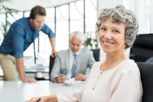 Close up face of executive businesswoman sitting in office while her team working in background. Portrait of smiling business woman sitting at desk and looking at camera. Happy senior woman satisfied with her company.